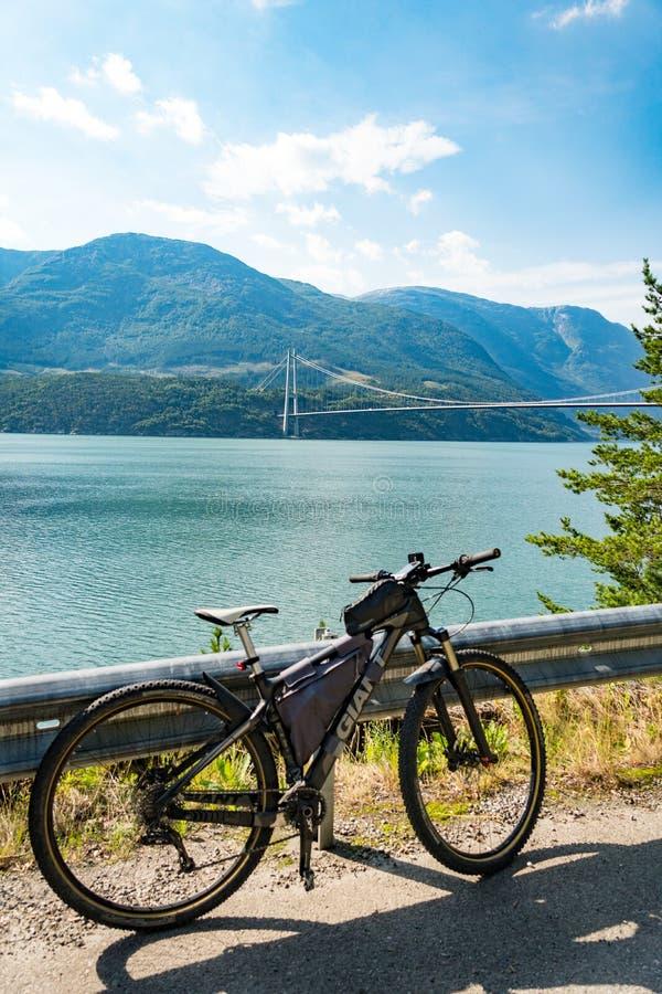 Theme of mountain biking in Scandinavia. human tourist in helmet and sportswear on bicycle in Norway on Hardanger Bridge royalty free stock image