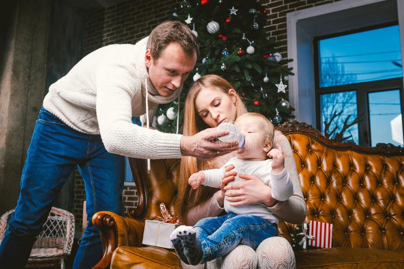 Theme new year and Christmas holidays in family atmosphere. Mood celebrate caucasian young mom dad and son. The father feeds the. Baby from bottle. boy drinks stock photo