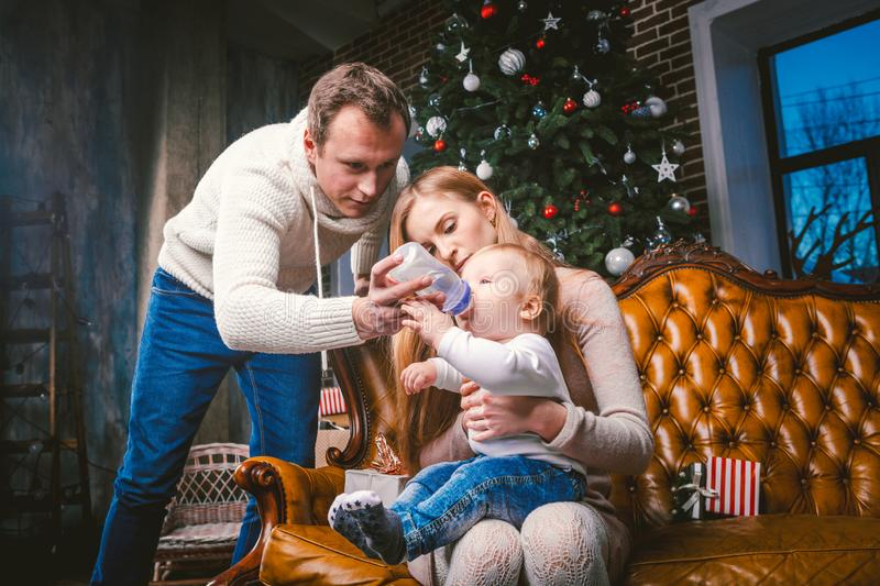 Theme new year and Christmas holidays in family atmosphere. Mood celebrate caucasian young mom dad and son. The father feeds the. Baby from bottle. boy drinks royalty free stock photos