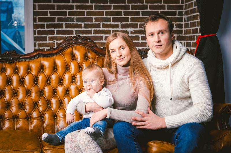 Theme new year and Christmas holidays in family atmosphere. Mood celebrate Caucasian young mom dad and son 1 year old sit on a royalty free stock photo