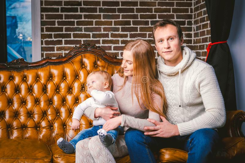 Theme new year and Christmas holidays in family atmosphere. Mood celebrate Caucasian young mom dad and son 1 year old sit on a. Leather brown sofa at home in stock photography