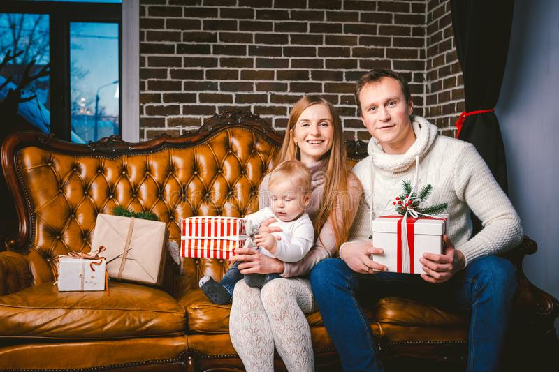 Theme new year and Christmas holidays in family atmosphere. Mood celebrate Caucasian young mom dad and son 1 year old sit on a. Leather brown sofa at home in stock images