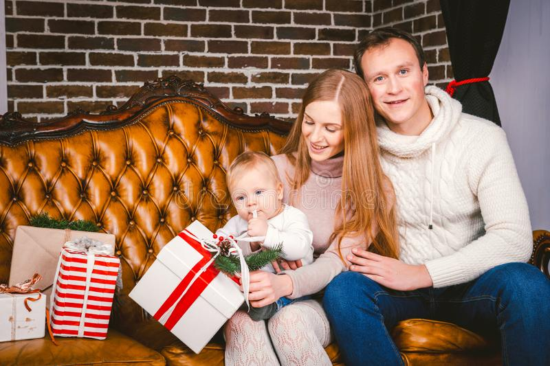Theme new year and Christmas holidays in family atmosphere. Mood celebrate Caucasian young mom dad and son 1 year old sit on a. Leather brown sofa at home in royalty free stock photography