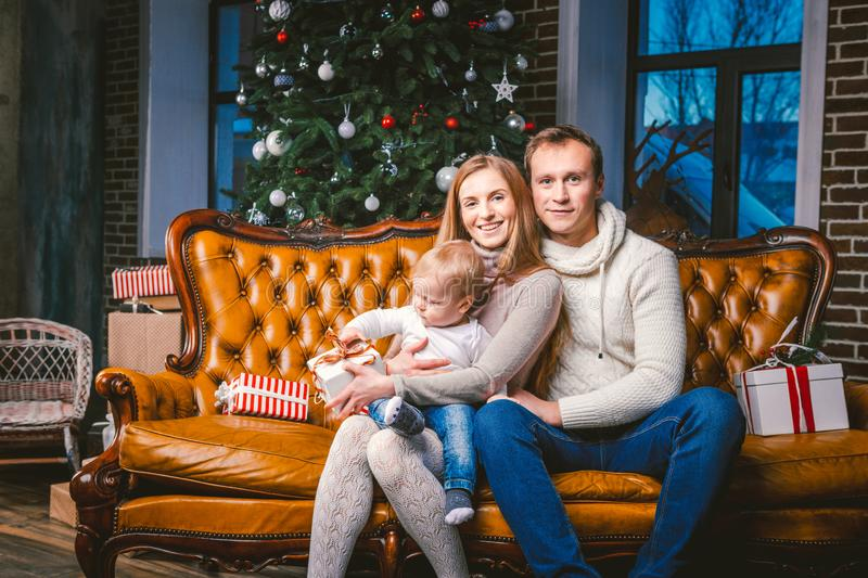 Theme new year and Christmas holidays in family atmosphere. Mood celebrate Caucasian young mom dad and son 1 year old sit on a. Leather brown sofa at home in stock photos