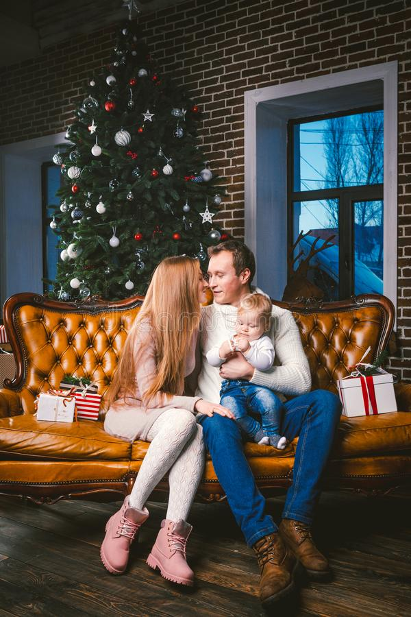 Theme new year and Christmas holidays in family atmosphere. Mood celebrate Caucasian young mom dad and son 1 year old sit on a royalty free stock image