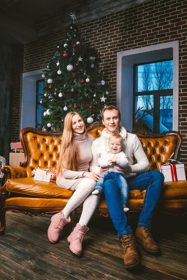 Theme new year and Christmas holidays in family atmosphere. Mood celebrate Caucasian young mom dad and son 1 year old sit on a stock photography