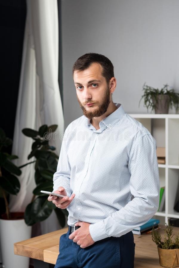 Theme office business. Handsome young caucasian man confident and strong with beard standing in bright room on working place. dres. Sed stylishly shirt and stock photos