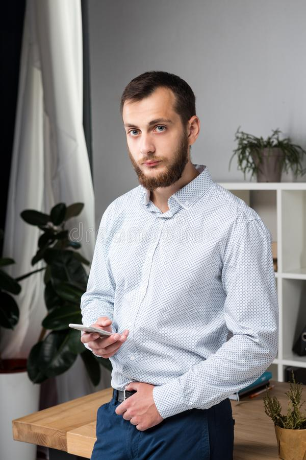 Theme office business. Handsome young caucasian man confident and strong with beard standing in bright room on working place. Dressed stylishly shirt and royalty free stock photo