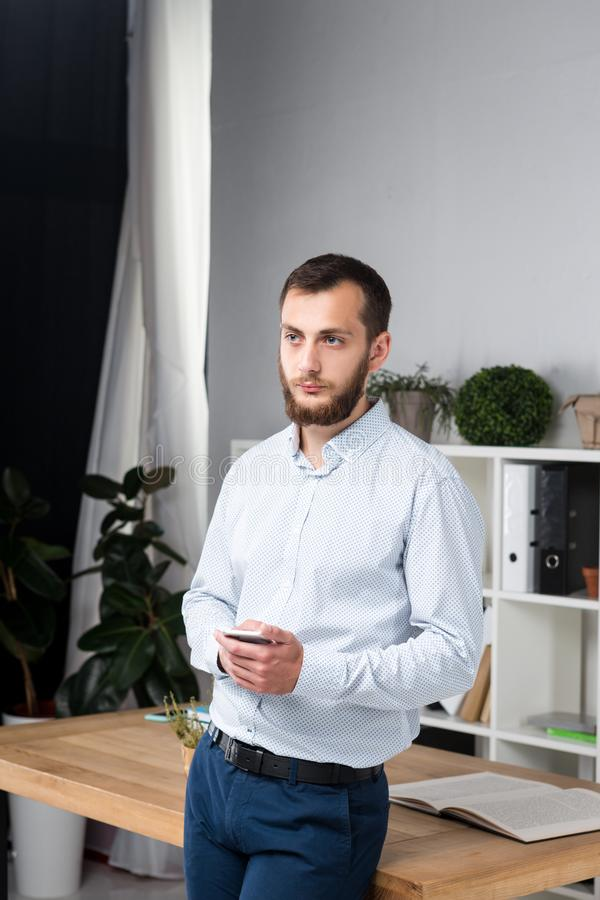 Theme office business. Handsome young caucasian man confident and strong with beard standing in bright room on working place. Dressed stylishly shirt and royalty free stock image
