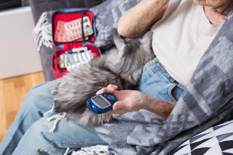 Theme old man and diabetes. Close-up of a hand. Senior Caucasian woman at home on the couch measures level of glucose in stock photography