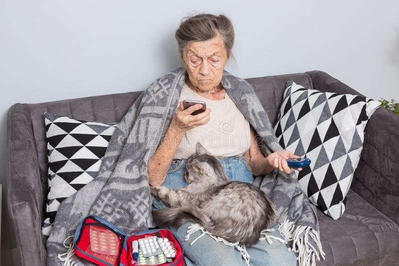 Theme old man and diabetes. older Caucasian woman with gray hair wrinkle home on sofa measures glucose level blood with stock image