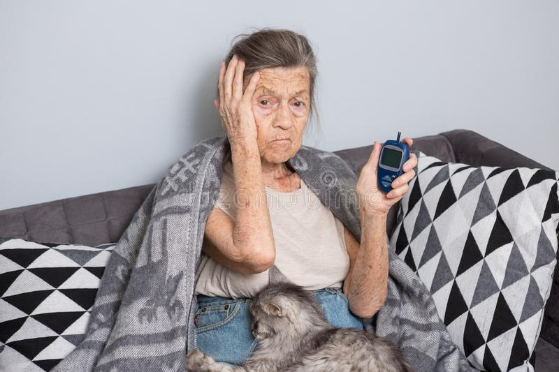Theme old man and diabetes. older Caucasian woman with gray hair and wrinkles home on sofa measures glucose level blood royalty free stock photo