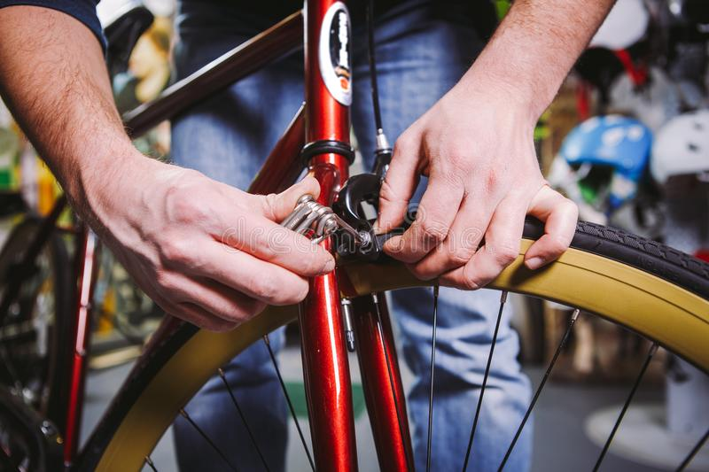 Theme repair bikes. Close-up of a Caucasian man`s hand use a hand tool hexagon set to adjust and install Rim Brakes on a red bicy. Cle stock photography