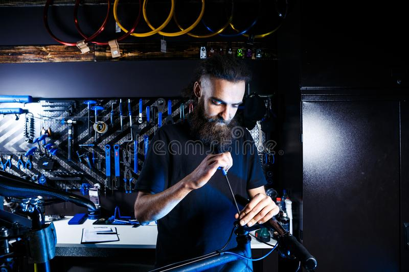 Theme sale and repair of bicycles. Young and stylish with a beard and long hair, a Caucasian man uses a tool to set up and repair stock photography