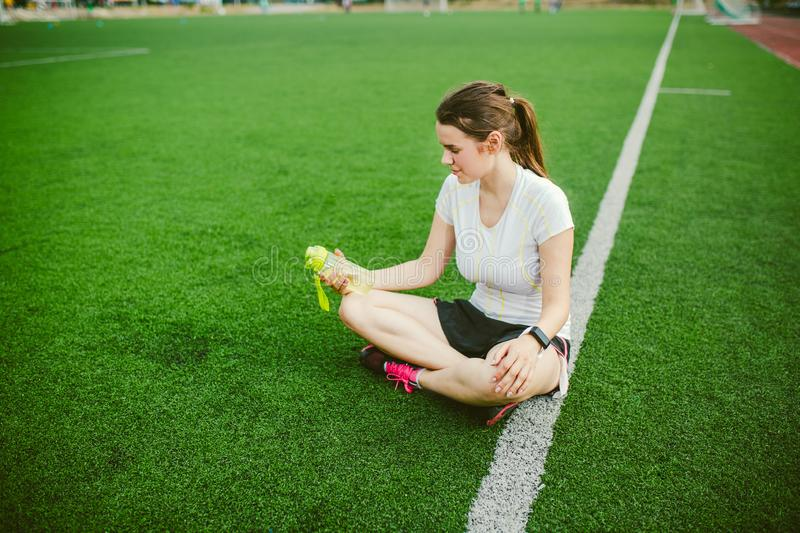 Theme sport and health. Beautiful young girl sitting resting on green grass, artificial turf stadium resting thirsty drink bottle stock photography