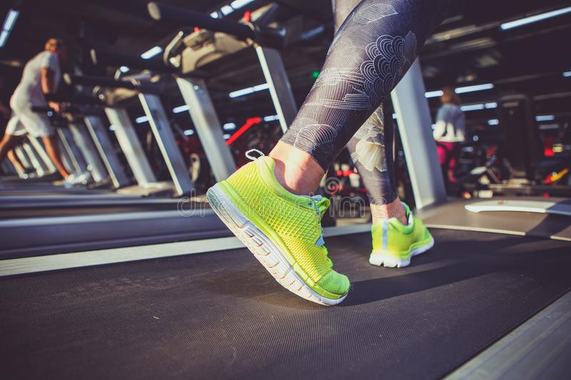 Theme of sport and weight loss. Close-up of the foot of a young strong woman in a light green sneakers on a simulator, running in stock photos