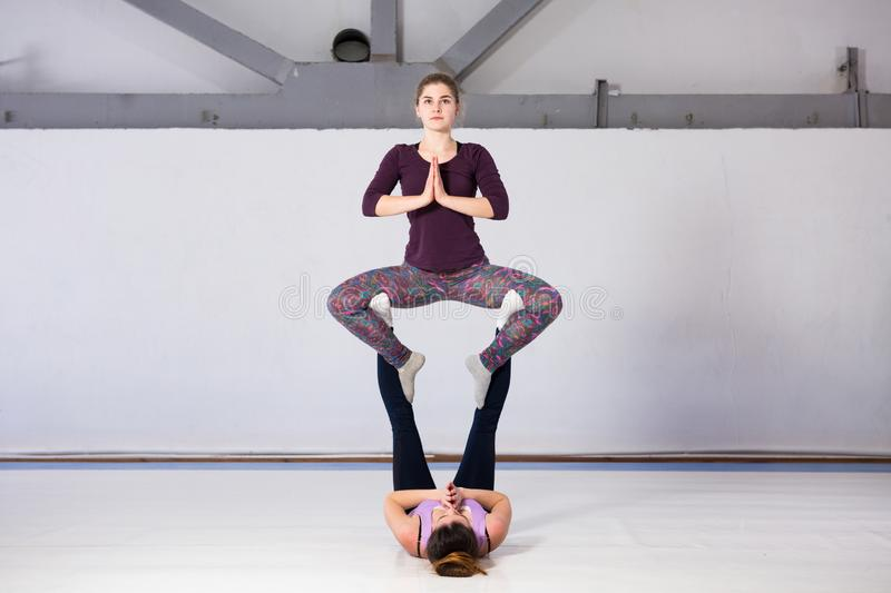 Theme sports health acrobatic yoga. A pair of two young Caucasian girls in the gym doing a throne posture base. Physical and royalty free stock photos