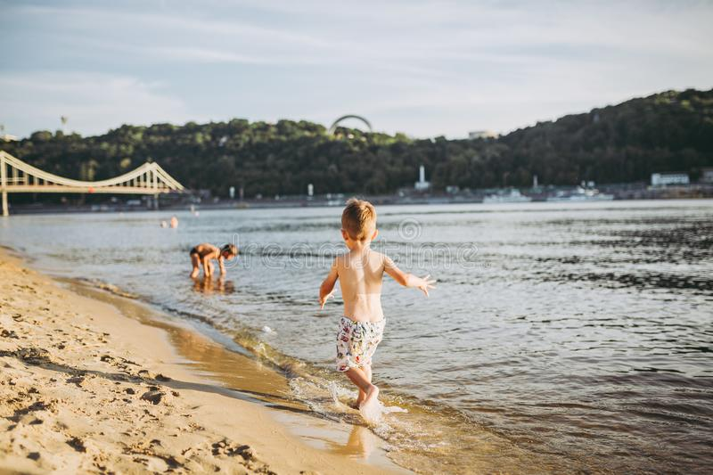 Theme summer outdoor activities near the river on the city beach in Kiev Ukraine. Little funny baby boy running along the river stock photo