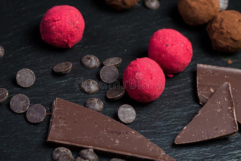 Theme sweet dessert cake handmade. Macro close-up dessert sweet candy round ball truffle set of black chocolate cocoa raspberry. Puer on a black background stock photography