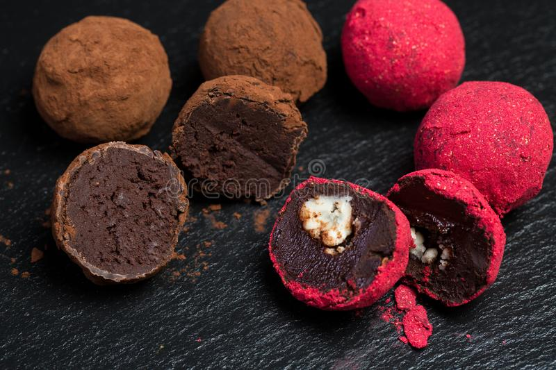 Theme sweet dessert cake handmade. Macro close-up dessert sweet candy round ball truffle set of black chocolate cocoa raspberry. Puer on a black background stock images