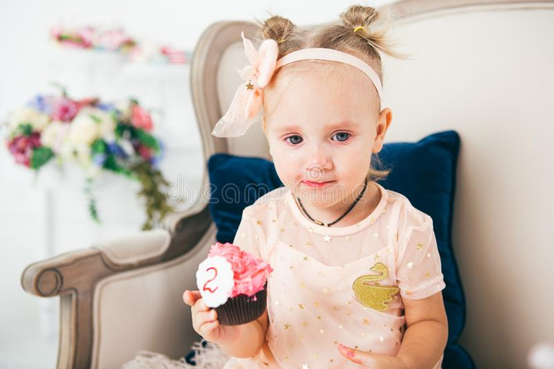 The theme is a sweet dessert cake with the symbol number two 2 for a child`s birthday. A little baby girl sits inside on a chair stock photos