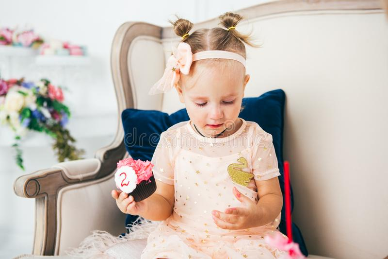 The theme is a sweet dessert cake with the symbol number two 2 for a child`s birthday. A little baby girl sits inside on a chair royalty free stock photography