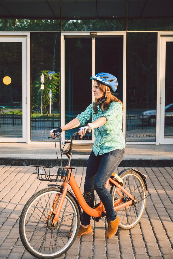Theme to work on the bike. A young Caucasian woman arrived on environmentally friendly transport bike to the office. Girl in a stock images