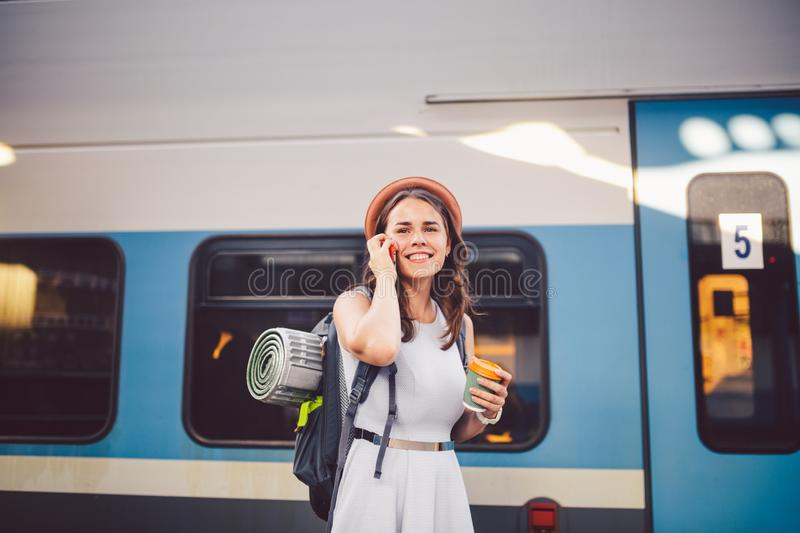 Theme tourism and travel young student. beautiful young Caucasian girl in dress and hat standing at train station near train with stock photos