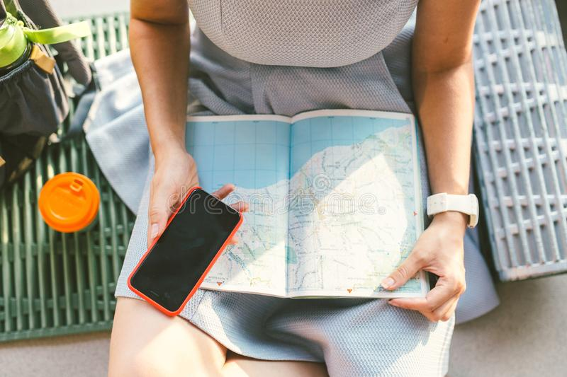 Theme travel planning. The top view hands Caucasian woman uses smart phone and studies the tourist map, passes route, navigates th royalty free stock photos