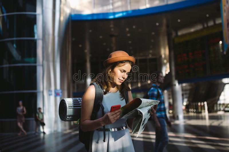 Theme travel and transportation. Beautiful young caucasian woman in dress and backpack standing inside train station terminal stock photos