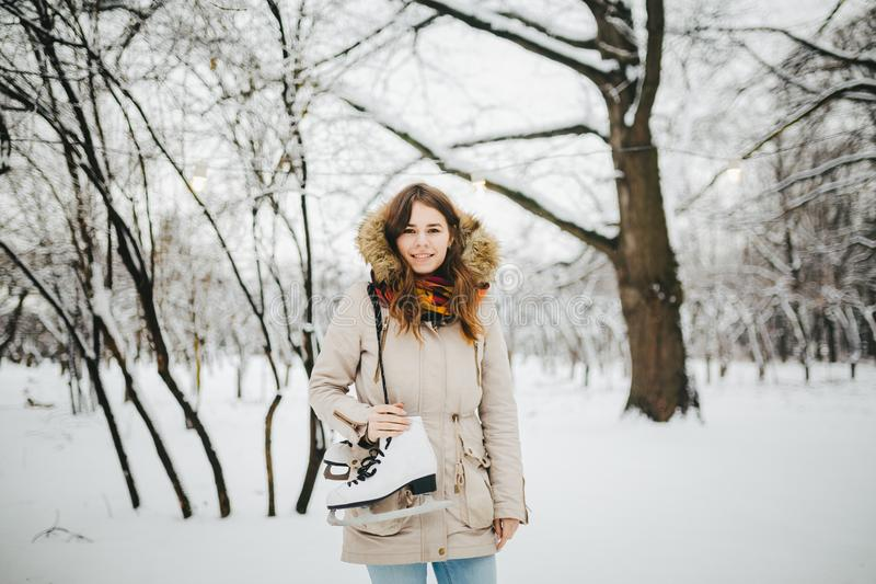 Theme is weekend holiday in winter. A beautiful young Caucasian woman stands in a snow covered park in jacket with hood and fur in stock photography