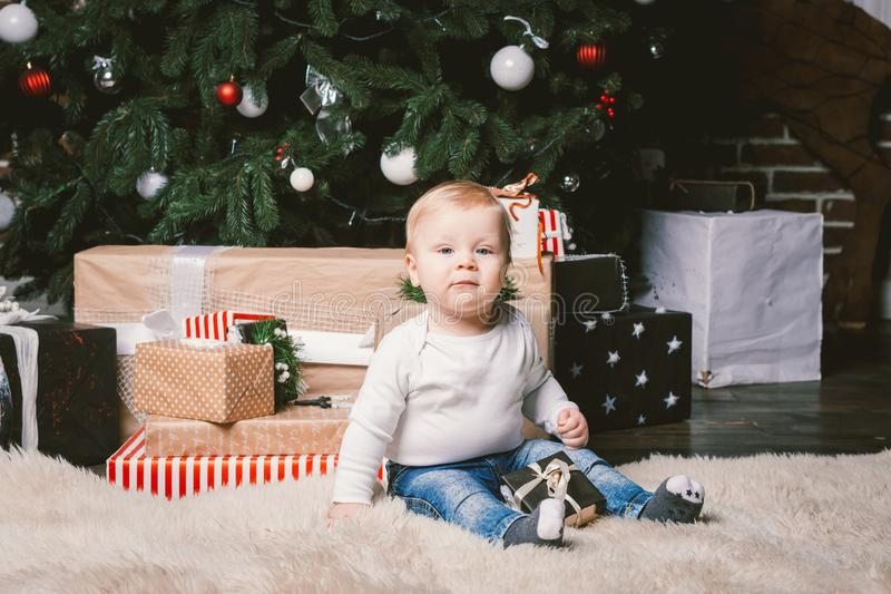 Theme winter and Christmas holidays. Child boy Caucasian blond 1 year old sitting home floor near Christmas tree with New Year dec royalty free stock photos