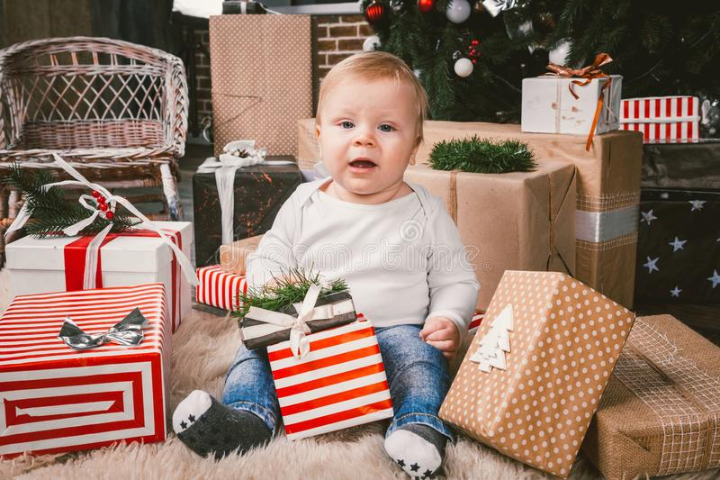 Theme winter and Christmas holidays. Child boy Caucasian blond 1 year old sitting home floor near Christmas tree with New Year dec royalty free stock image