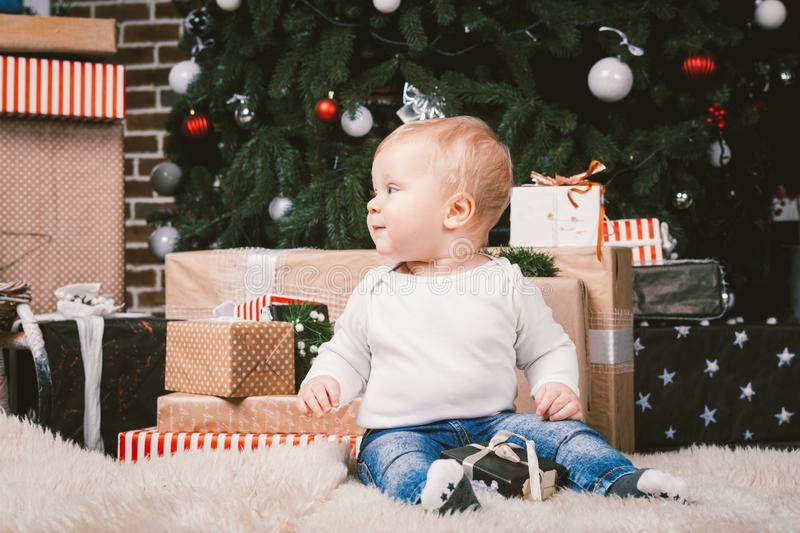 Theme winter and Christmas holidays. Child boy Caucasian blond 1 year old sitting home floor near Christmas tree with New Year dec royalty free stock photo