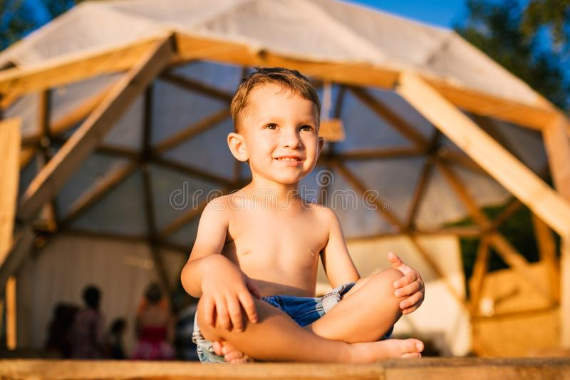 Theme is yoga and children. Caucasian Boy child sitting barefoot cross-legged in lotus position on wooden floor the. Background of gathering place of people. In stock photos