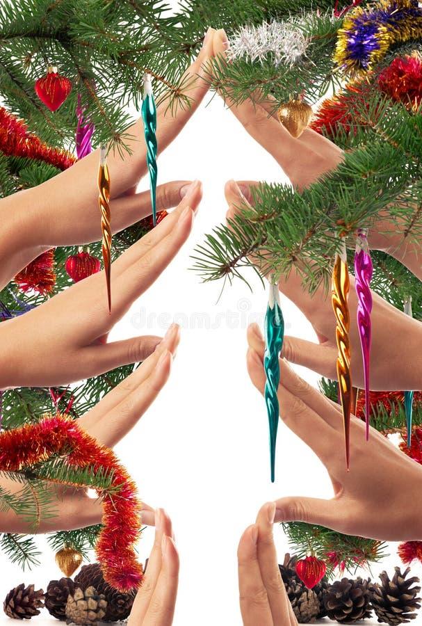 Themed begrepp för jul av händer som gör en julgranform som inramas med filialer och prydnader royaltyfria bilder