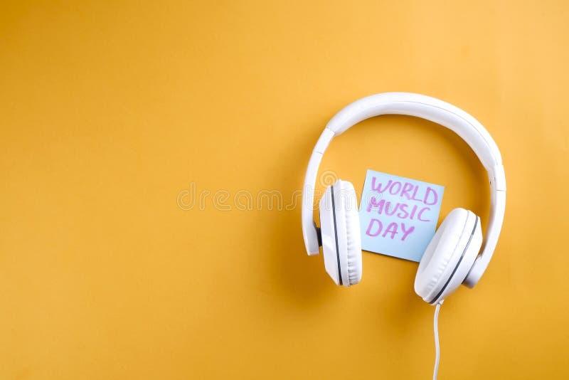 Themed sammansättning för världsmusikdag med vit hörlurar på gul bakgrund royaltyfria bilder