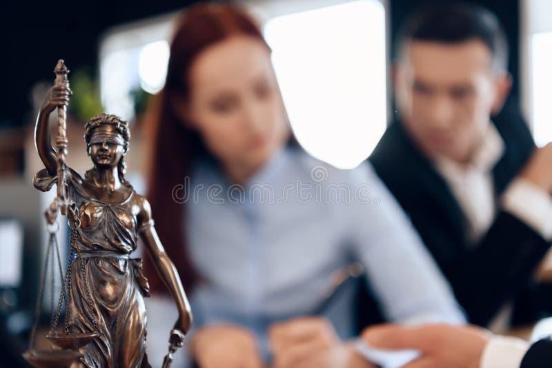 Themis古铜色雕象拿着正义标度  在未聚焦的背景中,夫妇签署文件 库存图片