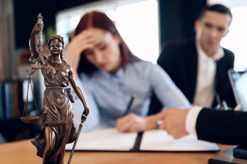 Themis古铜色雕象拿着正义标度  在未聚焦的背景中,夫妇签署文件 库存照片