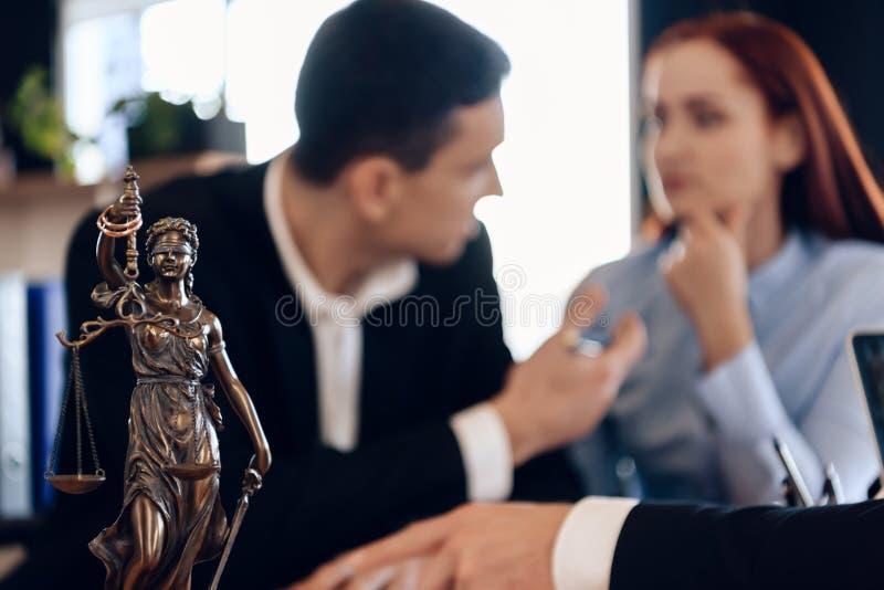 Themis古铜色雕象拿着正义标度  在未聚焦的背景中,成人签署文件 库存照片