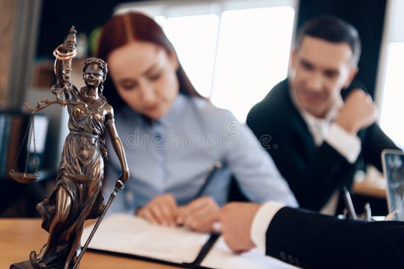 Themis古铜色雕象拿着正义标度  在未聚焦的背景中,成人签署文件 图库摄影