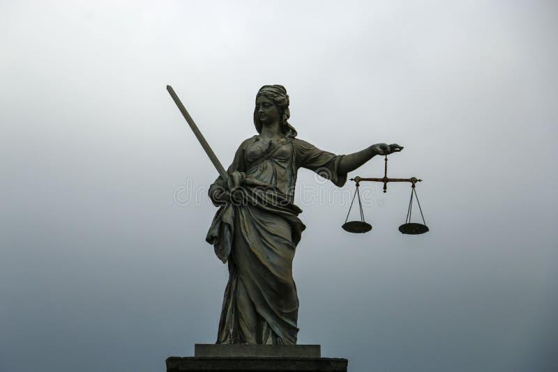 Themis雕象,正义的女神在灰色蓝色背景的 库存图片