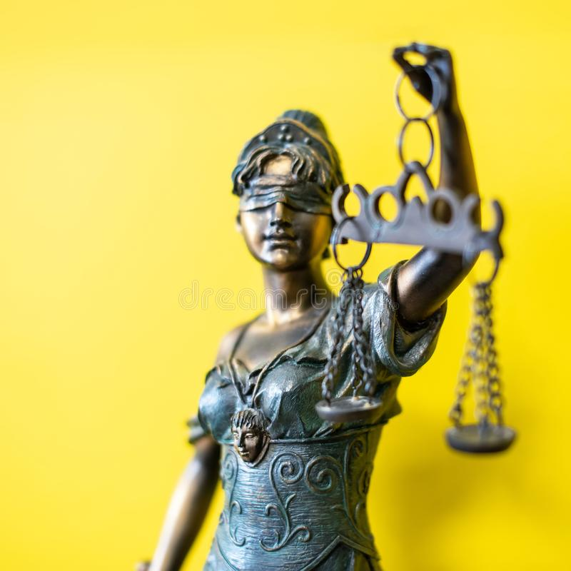 Themis Greek goddess of justice on yellow background. Themis ancient goddess of justice close-up on yellow background. metal figurine of the goddess royalty free stock images