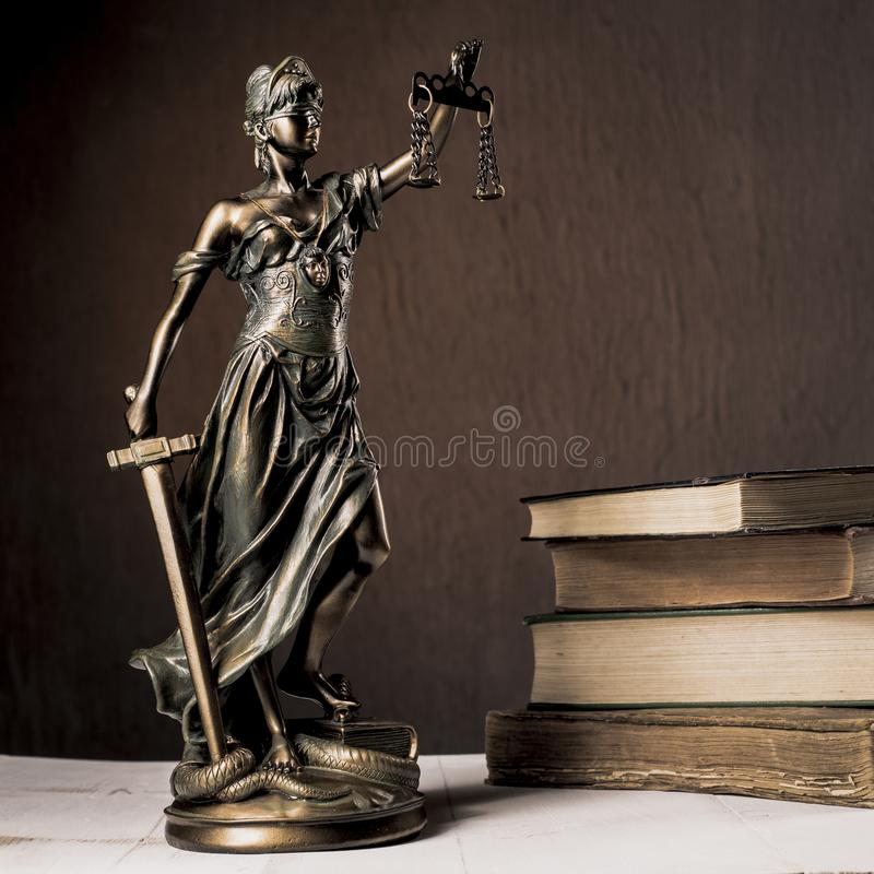 Themis figurine stands on a white wooden table next to a stack of old books stock images
