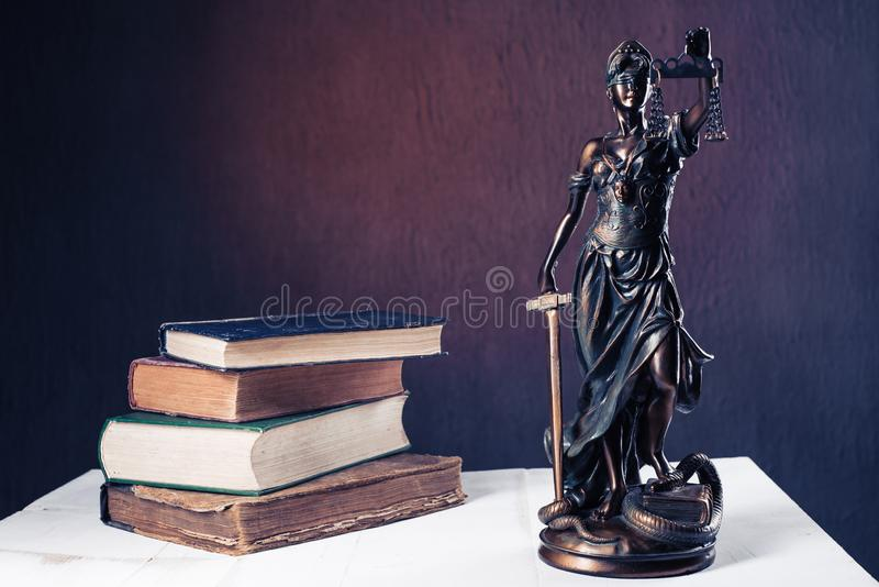 Themis figurine stands on a white wooden table next to a stack of old books royalty free stock images