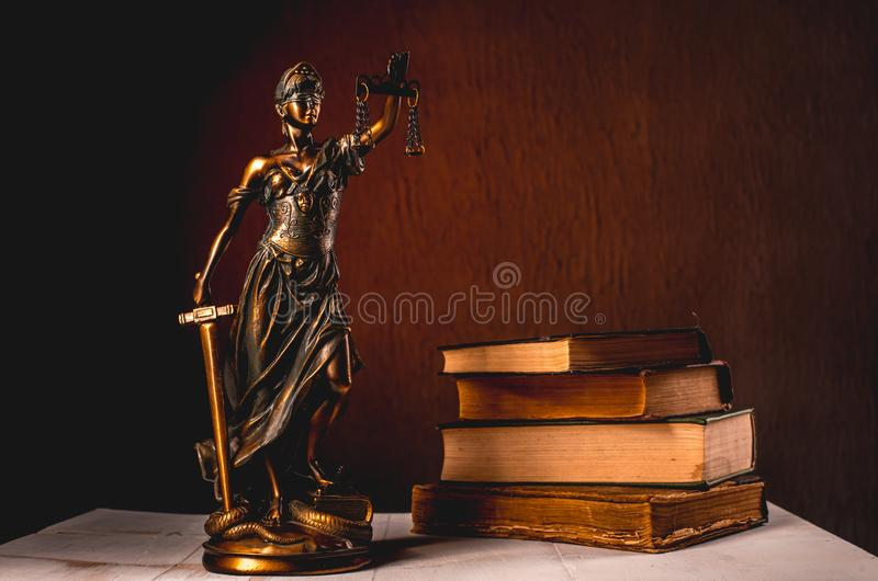 Themis figurine stands on a white wooden table next to a stack of old books stock photography