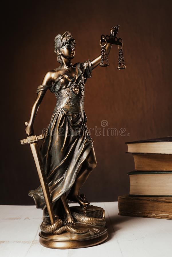 Themis figurine stands on a white wooden table next to a stack of old books stock image