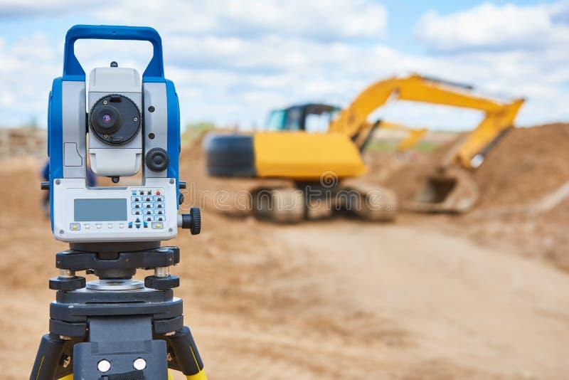 Theodolie d'équipement d'arpenteur au chantier de construction avec l'excavatrice photo stock