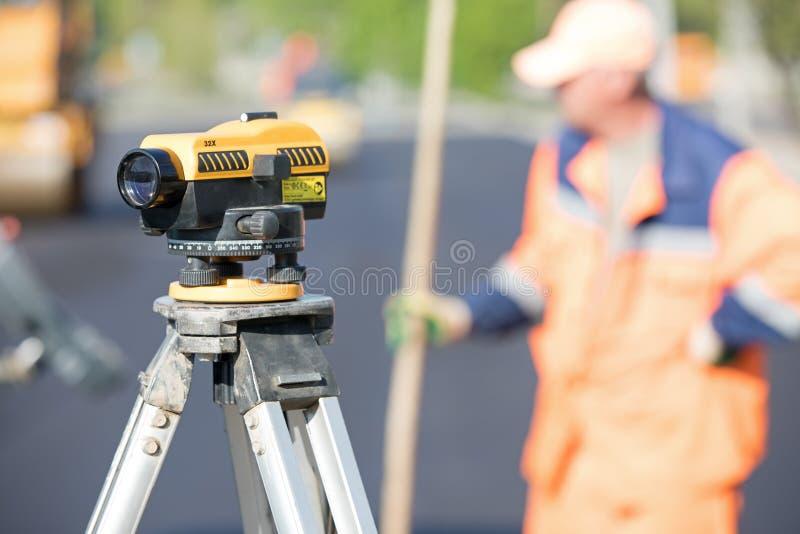 Theodoliethulpmiddel bij bouwwerf tijdens de wegwerken stock fotografie