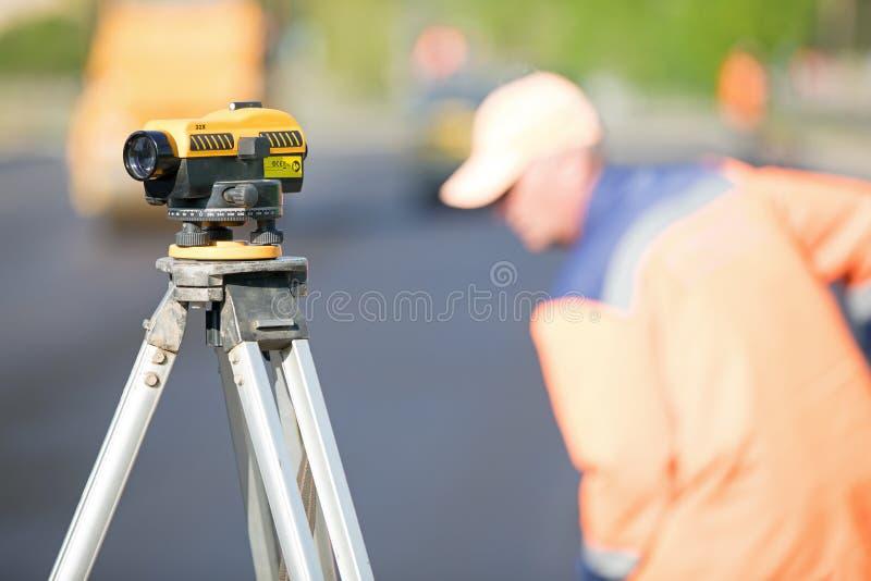 Theodoliethulpmiddel bij bouwwerf tijdens de wegwerken stock afbeeldingen
